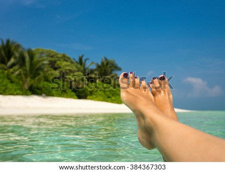 Close-up of female foot in the blue water on the tropical beach. Vacation holidays. - stock photo