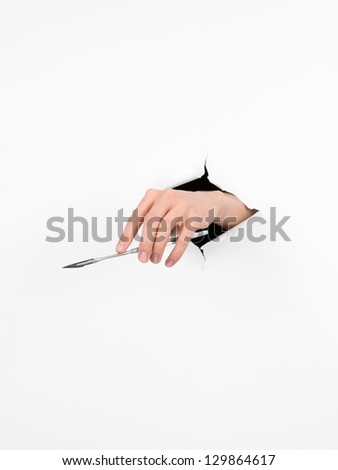 close-up of female hand holding a medical knife through a torn white paper, isolated - stock photo