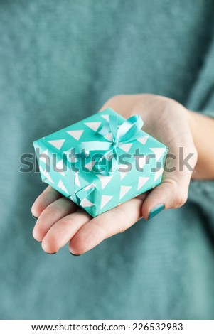 Close-up of female hand holding a present - stock photo
