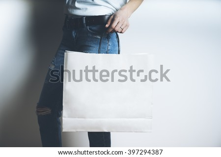 Close-up of female hand holding blank white paper package on white background, mock-up of white shopping bag with handles - stock photo