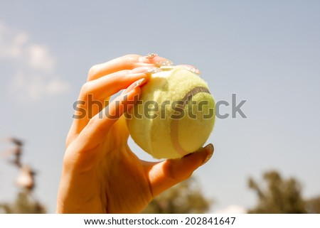 close up of female hand holding tennis ball - stock photo