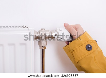 Close up of female hand in jacket adjusting radiator regulator to increase temperature - stock photo