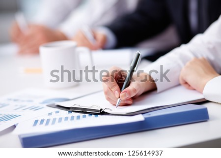 Close-up of female hand making notes - stock photo