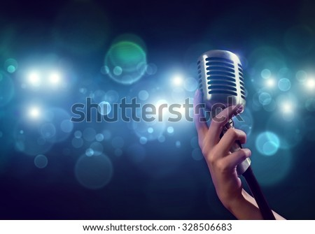 Close up of female hand on blurred background holding microphone  - stock photo