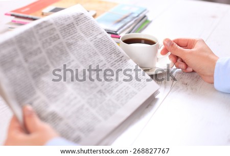 Close-up of female hand on cup of coffee during reading of newspaper - stock photo