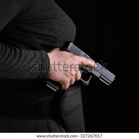 Close up of female hand pulled gun from the holster on a white background - stock photo