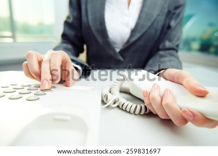 Close-up of female hand pushing buttons on telephone - stock photo