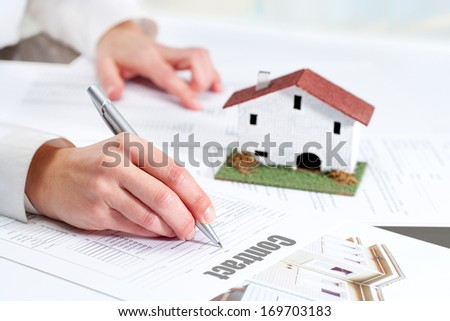Close up of female hand reviewing real estate contract. - stock photo