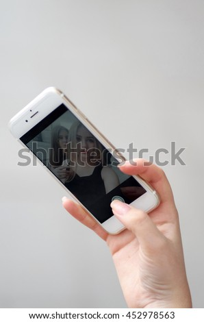Close-up of female hand, using a smart phone. Young Girl is typing to do selfie on her white smart phone/Hand Holding Smart phone with girls faces on the screen. Girl taking selfie  - stock photo