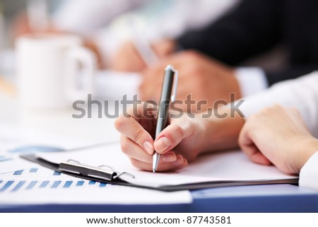 Close-up of female hand with pen over paper making notes - stock photo