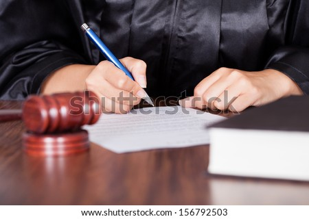 Close-up Of Female Hand Writing On Paper In Courtroom - stock photo