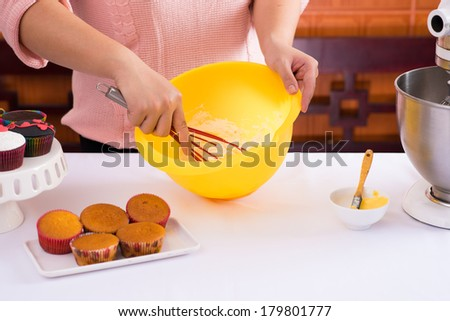 Close-up of female hands beating dough in the kitchen equipment on the foreground  - stock photo