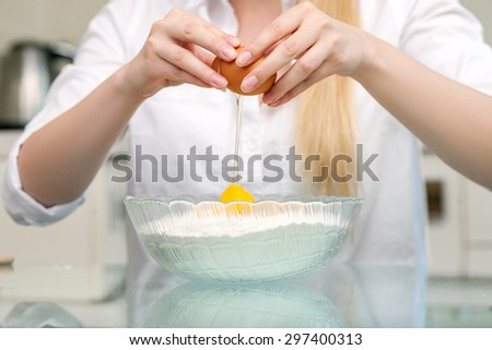 Close up of female hands chopping an egg into the bowl of flour - stock photo