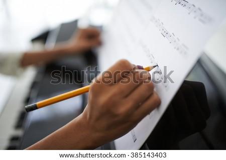 Close-up of female hands correcting music score - stock photo