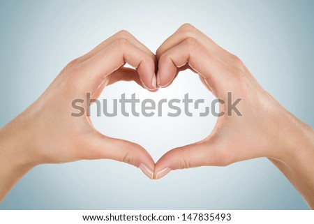 Close up of female hands form heart shape isolated on blue background - stock photo