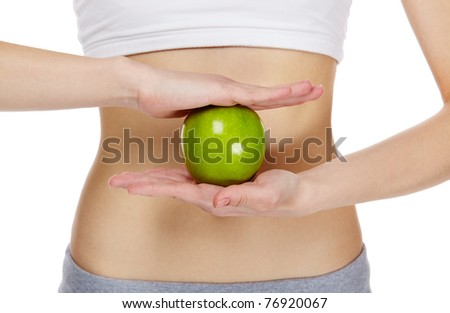 Close-up of female hands holding an apple in front of belly - stock photo