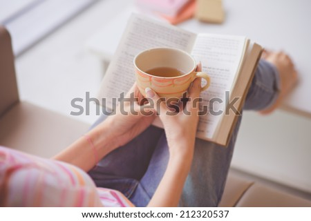 Close-up of female hands holding teacup in front of opened book - stock photo