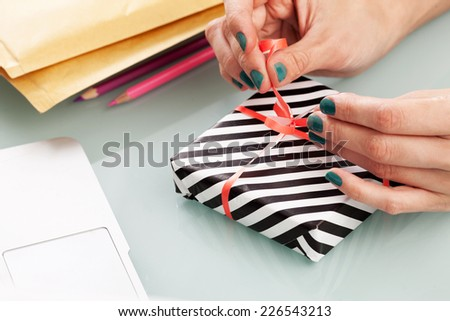 Close-up of female hands packing a present. - stock photo