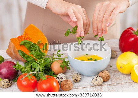 Close up of female hands ripping parsley into the bowl of crashed eggs. The woman is standing. There are a variation of fruits and vegetables on the table - stock photo