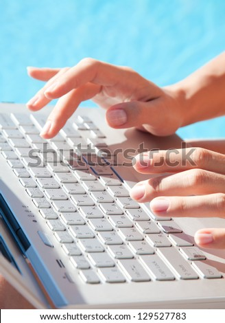 Close-up of female hands typing on a laptop in front of the pool - stock photo