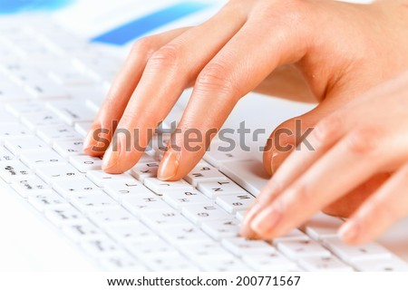 Close up of female hands typing on keyboard - stock photo