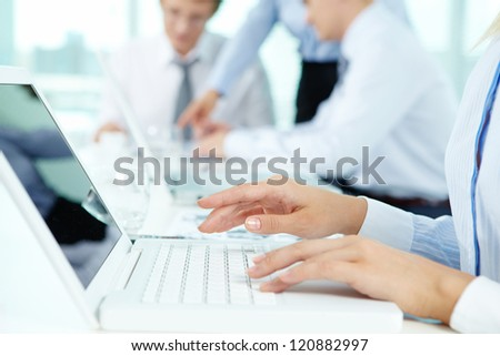 Close-up of female hands typing on the laptop keyboard - stock photo