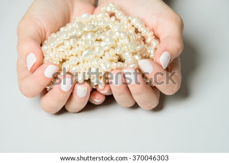 Close Up of Female Hands Wearing White Nail Polish and Cupping Long Strand of Pearls in Palms on Neutral Gray Surface with Copy Space - stock photo