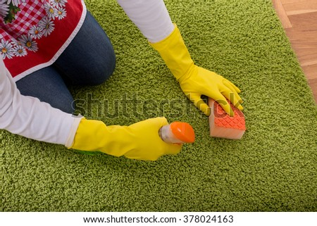 Close up of female hands with protective gloves cleaning carpet with sponge and liquid detergent from spray bottle - stock photo