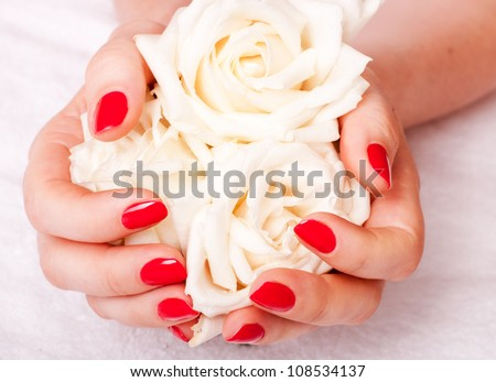 close-up of female hands with red nail polish on the background  flowers - stock photo