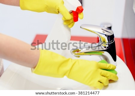 Close up of female hands with rubber gloves spraying liquid detergent on tap and cleaning it with sponge. Spring cleaning - stock photo