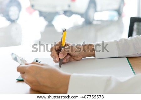 Close-up of female hands. Woman writing something and holding credit card. purchase concept  - stock photo