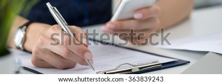 Close-up of female hands. Woman writing something and looking at mobile phone screen sitting at her office. Letter box format - stock photo