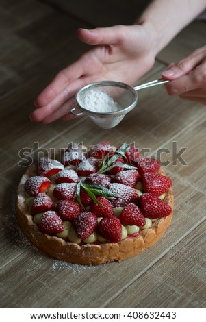 Close up of female pastry chef's hand decorating  top of delicious French strawberry cake. Cooking dessert in the kitchen. Close up, selective focus. - stock photo