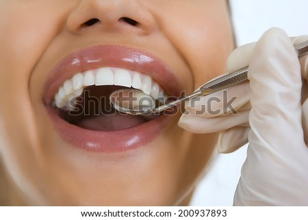 Close-up of female patient having her teeth examined by dentist, visit to the dentist, oral checkup with mirror   - stock photo