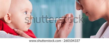 Close-up of female pediatrician examining baby's throat - stock photo