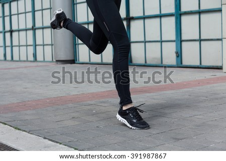 Close-up of female runner's slim muscled legs - stock photo