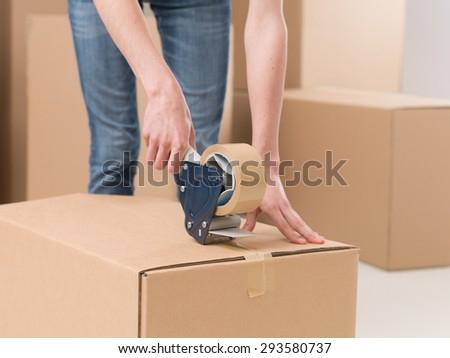 close-up of female sealing cardboard box with adhesive tape - stock photo