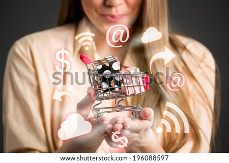 Close up of female shopper with little shopping chart in hands surrounds shopping icons - stock photo