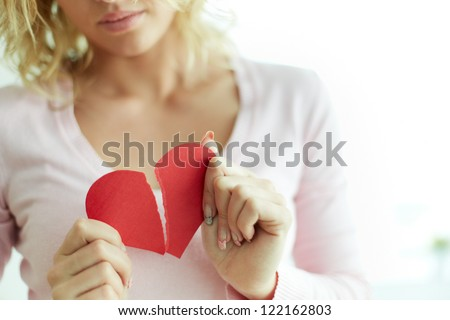 Close-up of female showing red broken paper heart - stock photo