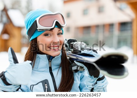 Close up of female wearing sports jacket and goggles who hands skis and thumbs up - stock photo