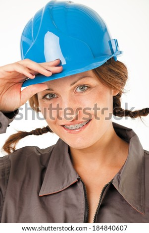 Close-up of  female worker with hardhat and braces smiling, studio on white - stock photo
