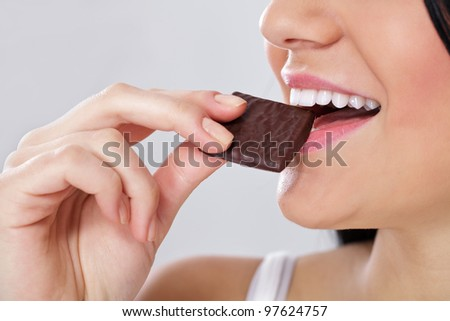 close up of females mouth with slice of the chocolate - stock photo