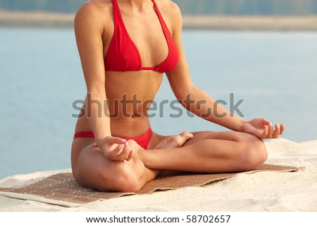 Close-up of females torso during meditation with legs crossed on summer vacation - stock photo