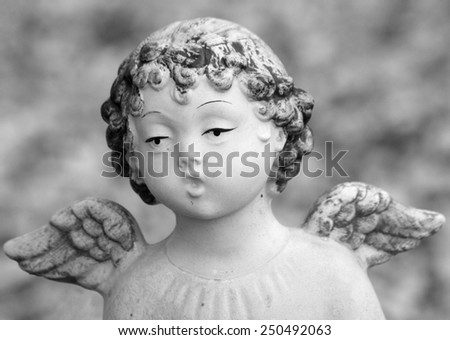 close up of figurine of singing little  winged angel  - stock photo