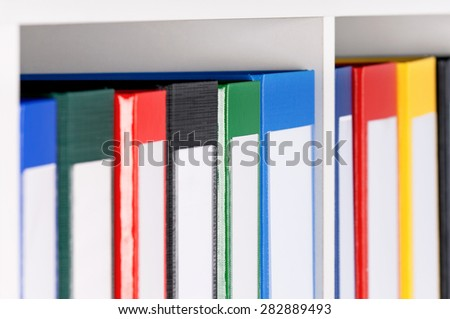 Close up of file folders, standing on the shelves  - stock photo