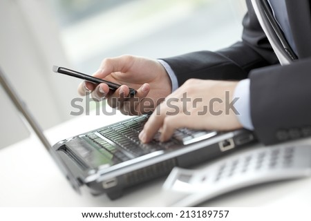 Close-up of financial advisor analyzing data while using his mobile phone. Business people.  - stock photo