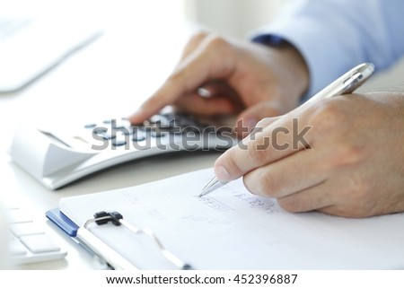 Close-up of financial businessman calculating tax expenses while sitting at office in front of computer. - stock photo