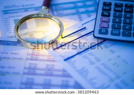Close-up of financial documents with magnifying glass and calculator. - stock photo
