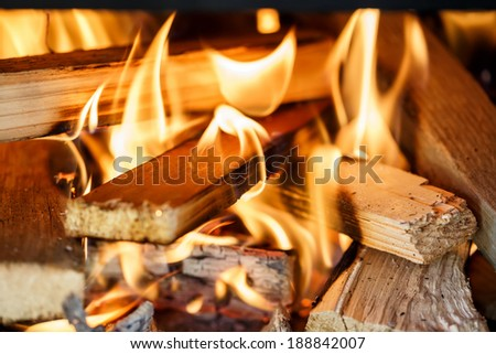 Close up of firewood burning in outdor fireplace - stock photo