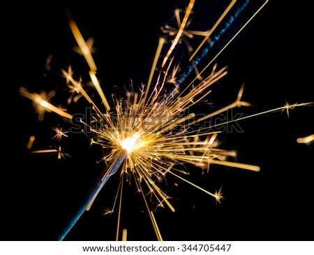 close-up of firework sparkler burning on black background, congratulation greeting  party happy new year,  christmas celebration concept - stock photo